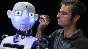 No matter what face you put on it, science is a powerful tool. Here, engineer Marcus Hold works on a nearly completed RoboThespian. Marvels of modern science, these fully interactive and multilingual humanoid robots are increasingly being sold to academic research groups.
