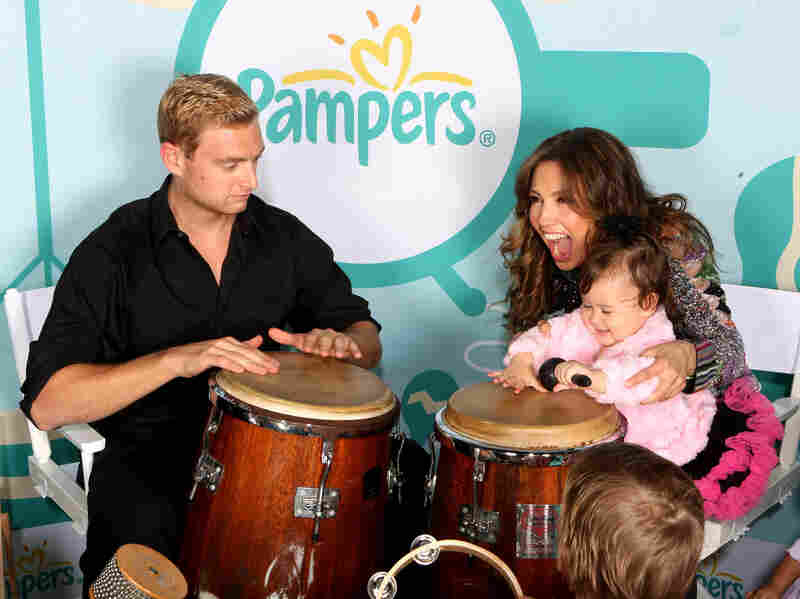 Latina pop star Thalía holds a toddler playing a tumbadora during a Pampers promotional event launching Mi Música, Mi Herencia (My Music, My Heritage).