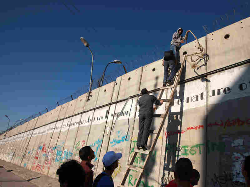 Palestinian men climb a section of Israel's separation barrier on Aug. 2. They were attempting to go from the West Bank to the Al-Aqsa mosque compound in Jerusalem's Old City to pray on the last Friday of the holy month of Ramadan.