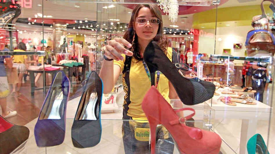 Camila DeSouza, a 17-year-old Brazilian, shops for shoes at a mall in Sunrise, Fla., on July 16, 20