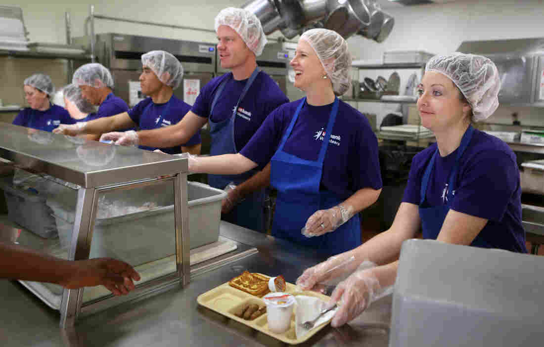 Kristin Yentes (right) and other volunteers from U.S. Bank serve breakfast to diners at Catholic Charities Opportunity Center in Minneapolis. Workers from the bank have been volunteering with Catholic Charities for more than a year.