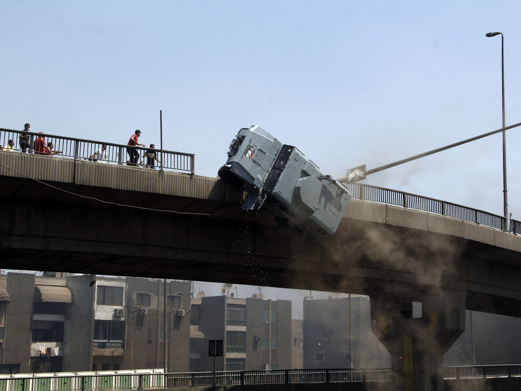 "Protesters pushed a police vehicle off of the 6th of October bridge in Nasr City. ""It looks like a war zone,"" NPR's Leila Fadel reported from Cairo."