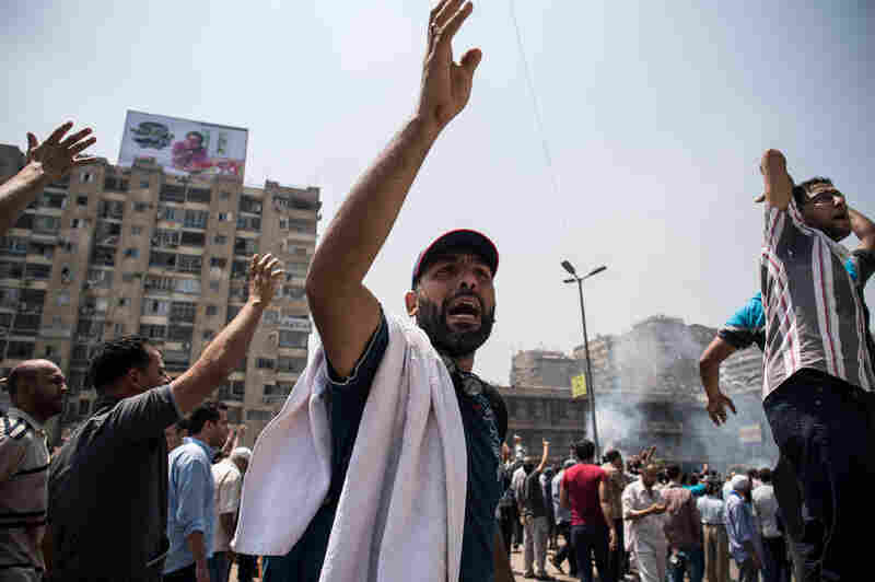 "Morsi supporters shout slogans in Cairo's Nasr City. In a televised statement, U.S. Secretary of State John Kerry called for a political resolution, saying that ""violence is simply not a solution in Egypt or anywhere else."""