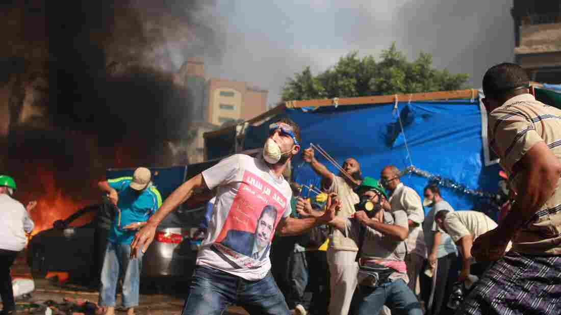 Supporters of the Muslim Brotherhood clash with the Egyptian security forces Wednesday in Cairo. In addition to the fighting, the interim government imposed a state of emergency.