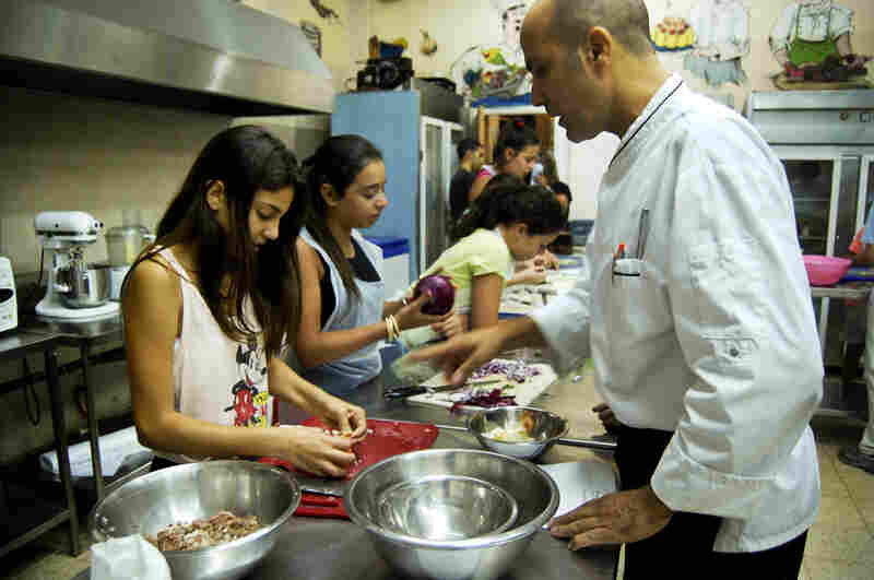 Chef Udi Shlomi advises Aviv Raz, 13, on prepping the kubbeh filling. Kubbeh hamusta, which Shlomi says originated in Kurdistan, has a vinegary-lemony taste.