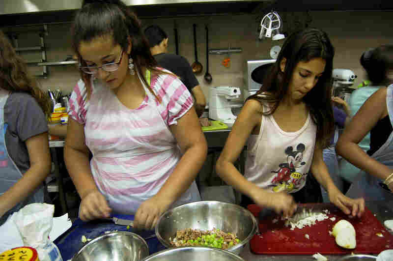 Adi Binyamin (left), 14, and Razs chop onions and celery for the kubbeh filling.