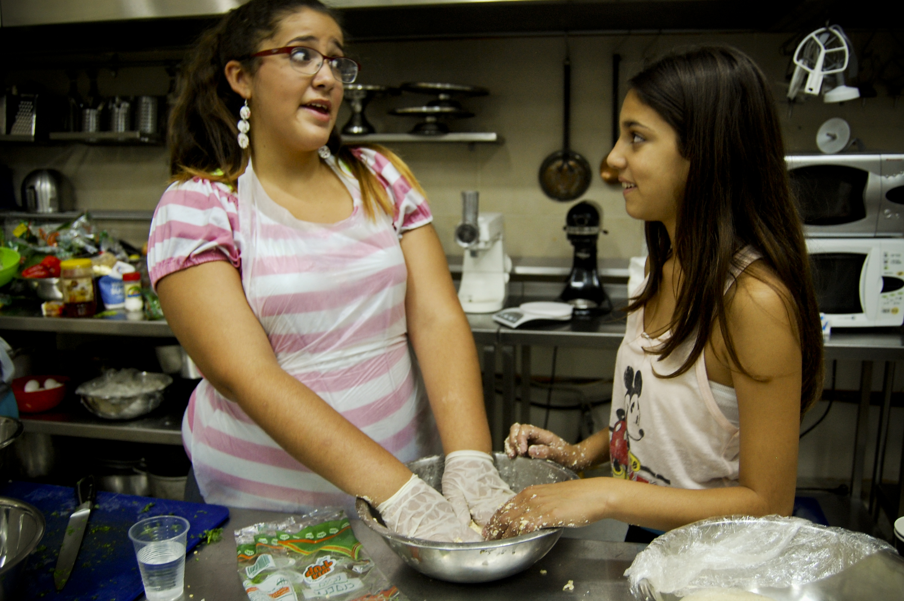 """Kubbeh dough feels weird!"" says Binyamin as she squeezes water into the semolina and bulgur mix."