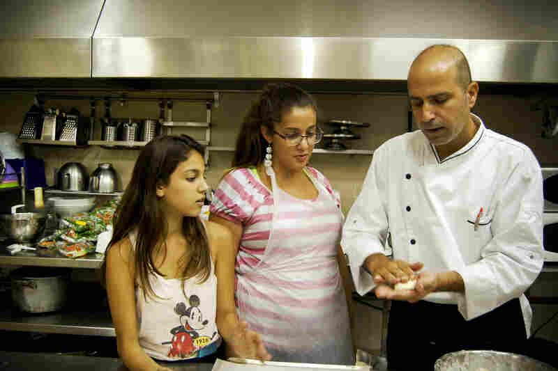 Chef Shlomi shows the campers how to fill a ball of dough with browned meat and pat the kubbeh smooth.