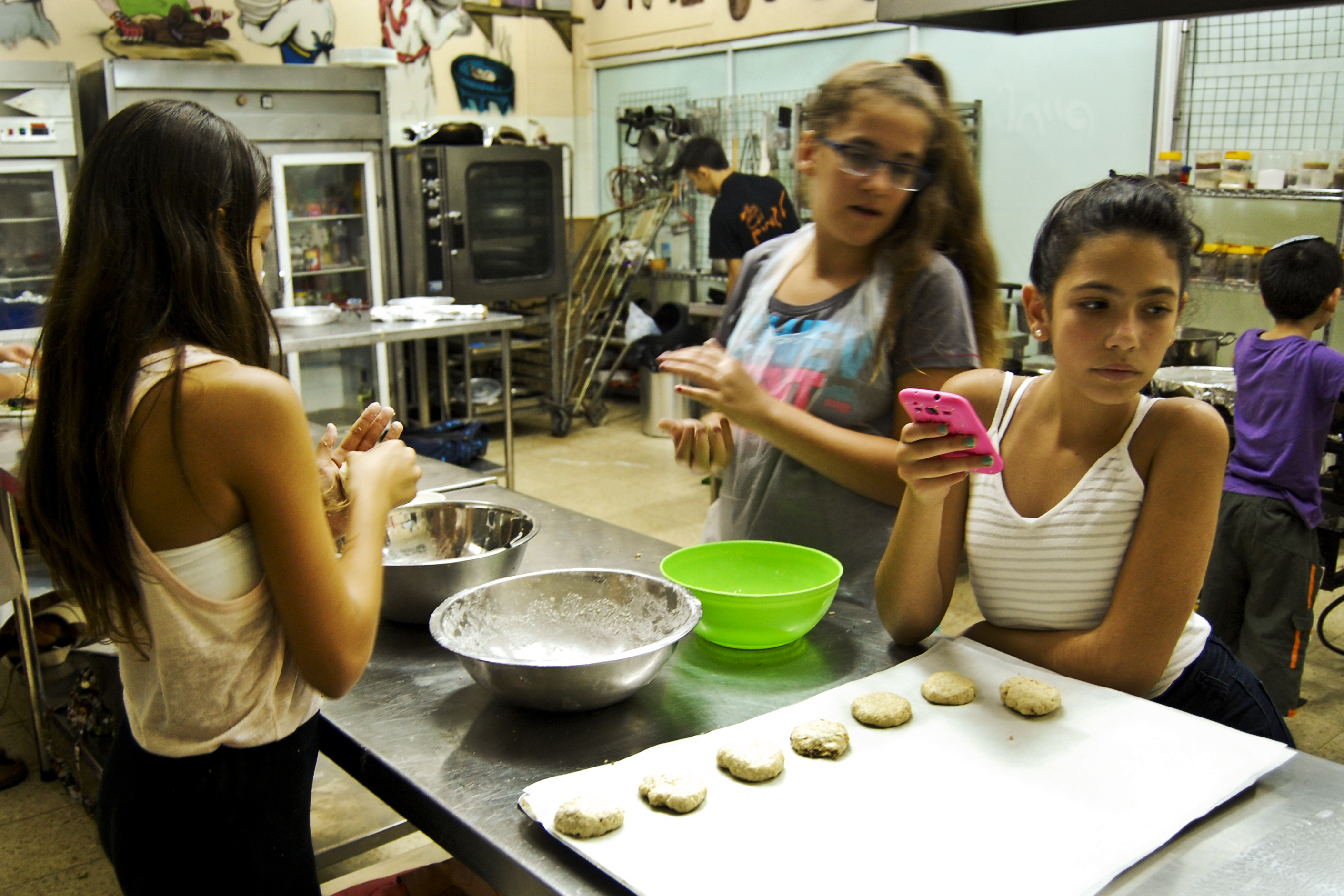 Noa Binyamin, 11, peeks at her friend's pink cell phone while shaping the dumpling mixture in her hands.