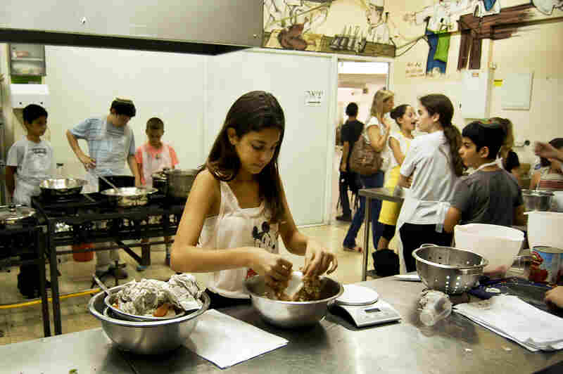 At cooking camp, Aviv Raz makes the filling for kubbeh hamusta, mixing onion into chopped beef. It's a beloved family dish her grandmother makes every Friday.