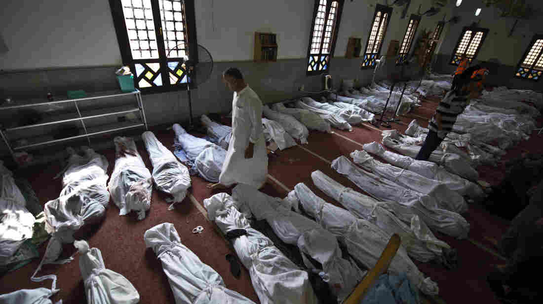 A man walks among shrouded bodies at a Cairo mosque on Thursday. At the El-Iman mosque, more than 200 bodies were being prepared for burial, the victims killed in a crackdown on protesters by Egypt's military-backed government.