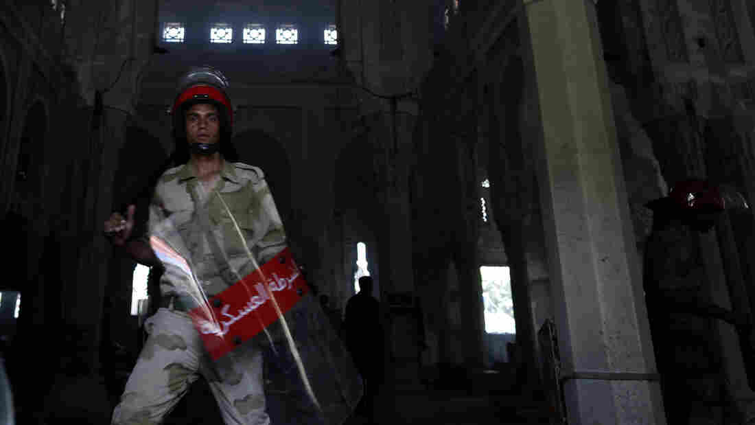 An Egyptian army soldier stands Thursday amid the charred remains of the R