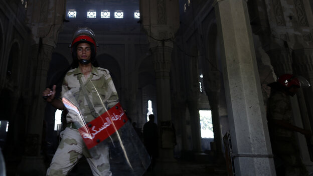 An Egyptian army soldier stands Thursday amid the charred remains of the Rabaah al-Adawiya mosque, in the center of the largest protest camp of supporters of ousted President Mohammed Morsi, that was cleared by security forces in Cairo on Wednesday.