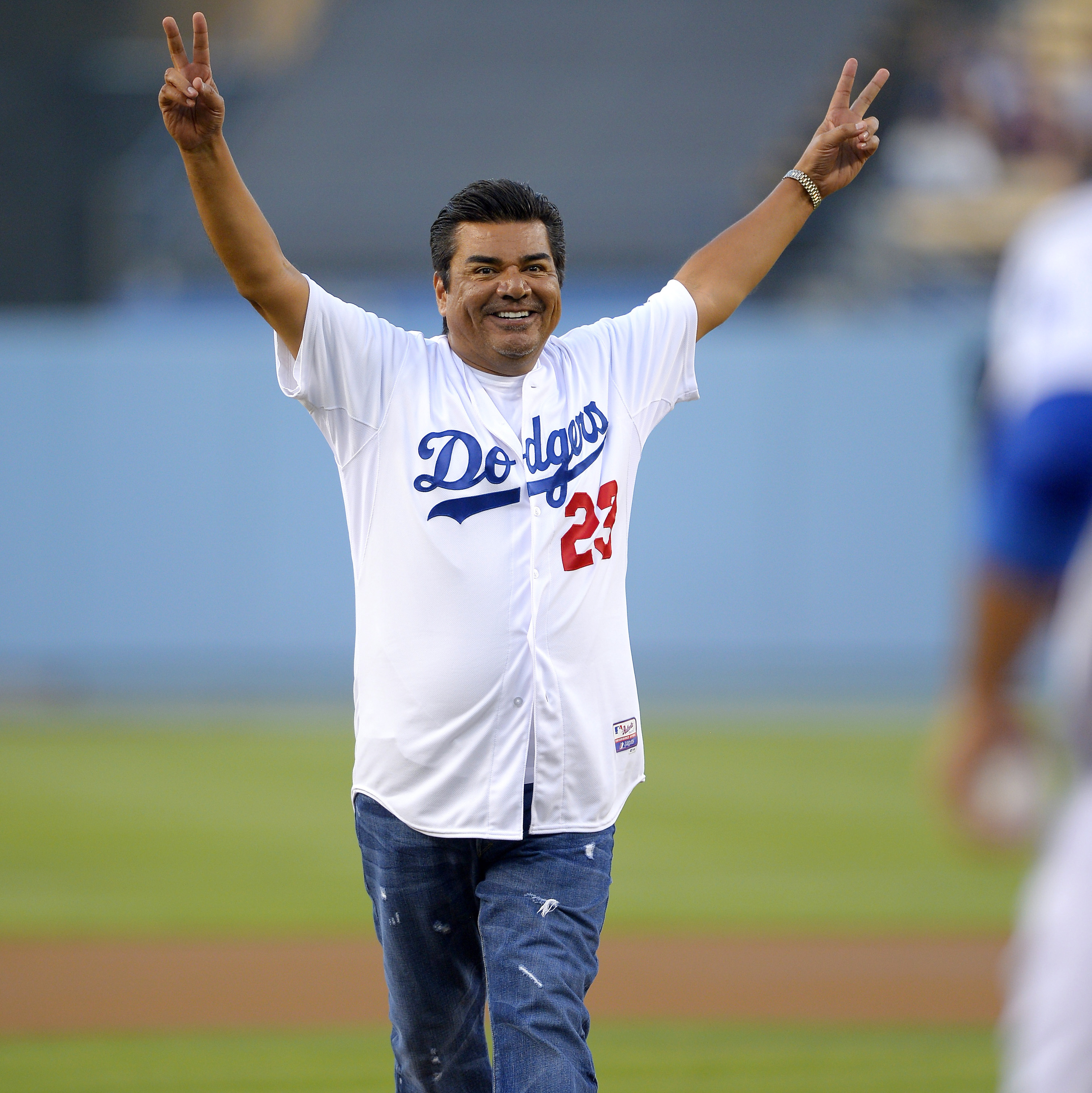 Comedian George Lopez leaves the mound after throwing out the ceremonial first pitch prior to the Los Angeles Dodgers' baseball game against the New York Mets on Wednesday.