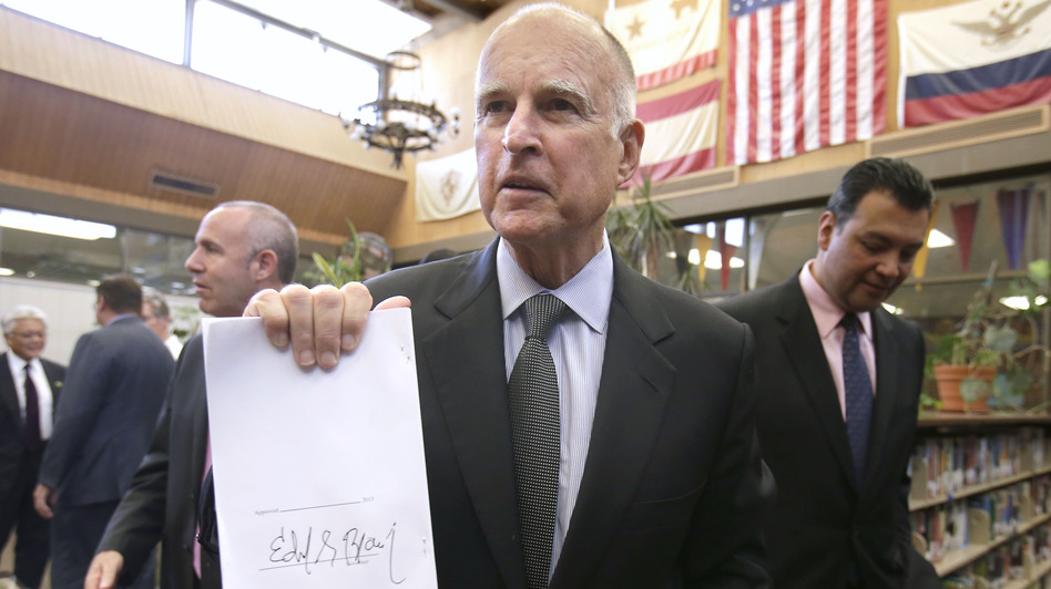 Gov. Jerry Brown holds up a copy of the education bill he signed during a ceremonial signing at California Middle School in Sacramento on July 1.
