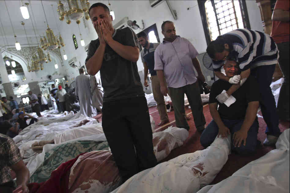Mourners stand over the bodies of loved ones at the El-Iman mosque in the Nasr City district of Cairo. Wednesday's violence was Egypt's worst since the 18-day uprising that ousted President Hosni Mubarak in 2011.