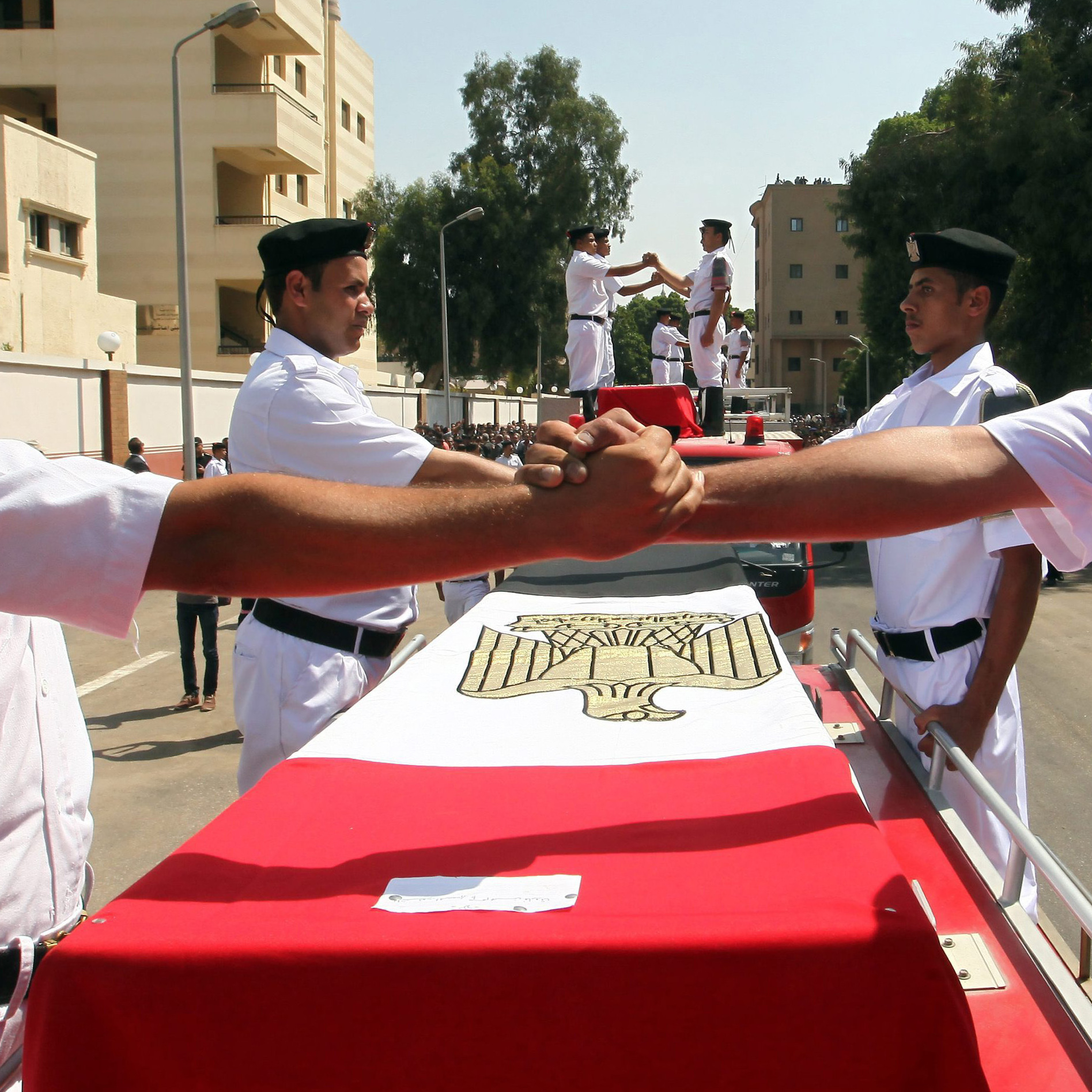 Egyptian police officers join hands during a funeral procession of one their colleagues, who was killed during clashes with Morsi supporters.