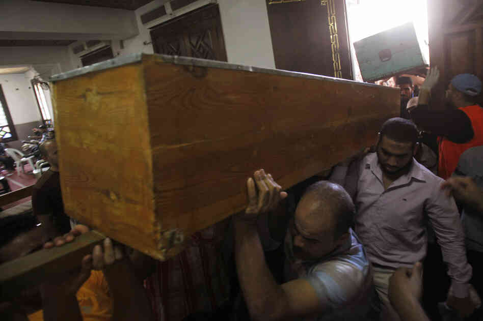 Members of the Muslim Brotherhood carry the coffin of a fellow member at the El-Iman mosque. The Muslim Brotherhood has vowed to continue their protests over Morsi's removal.