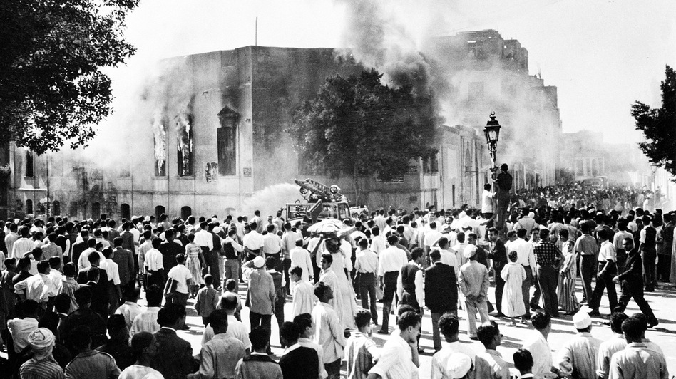 Crowds gather around the burning headquarters of the Muslim Brotherhood in Cairo on Oct. 27, 1954. The building was set on fire following the attempted assassination of President Gamal Abdel Nasser. (AP)