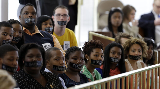 Opponents of North Carolina's new voter ID legislation wear tape over their mouths while sitting in the gallery of the House chamber of the North Carolina General Assembly in Raleigh, N.C., on April 24, where lawmakers debated new voter laws. On Monday, Gov. Pat McCrory signed a new law that requires a state-approved photo ID to