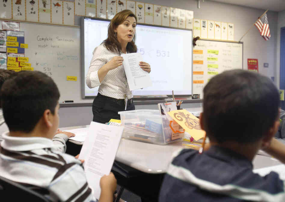 Second-grade teacher Vickie Boudouris goes over a worksheet in an English-learner summer school class at the Cordova Villa Elementary School in June, in Rancho Cordova, Calif. Under Gov. Jerry Brown's proposed budget, California schools will receive an additional $3.6 billion this year, with much of it targeted to the neediest students.