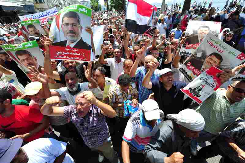 Supporters carry posters of Morsi and shout slogans during a march in Alexandria.