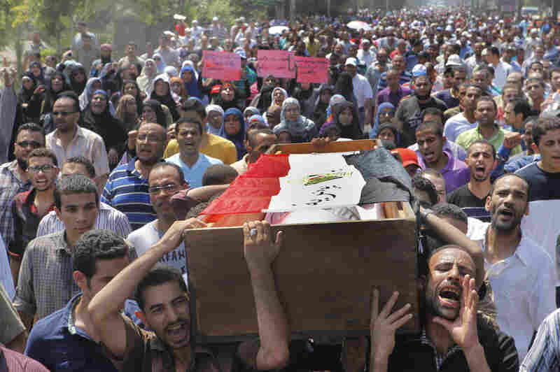 Morsi supporters march toward Old Cairo as they carry a coffin, covered with a national flag, of someone killed during Wednesday's clashes.
