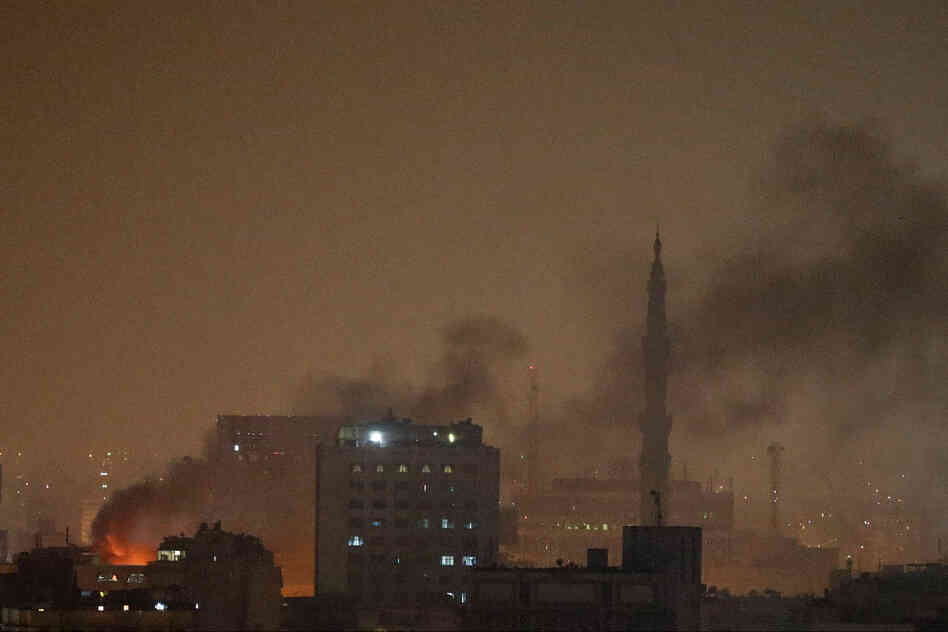 Smoke rises over Ramses Square after protests turned violent across Egypt. The government has imposed a night-time curfew set to last at least a month.