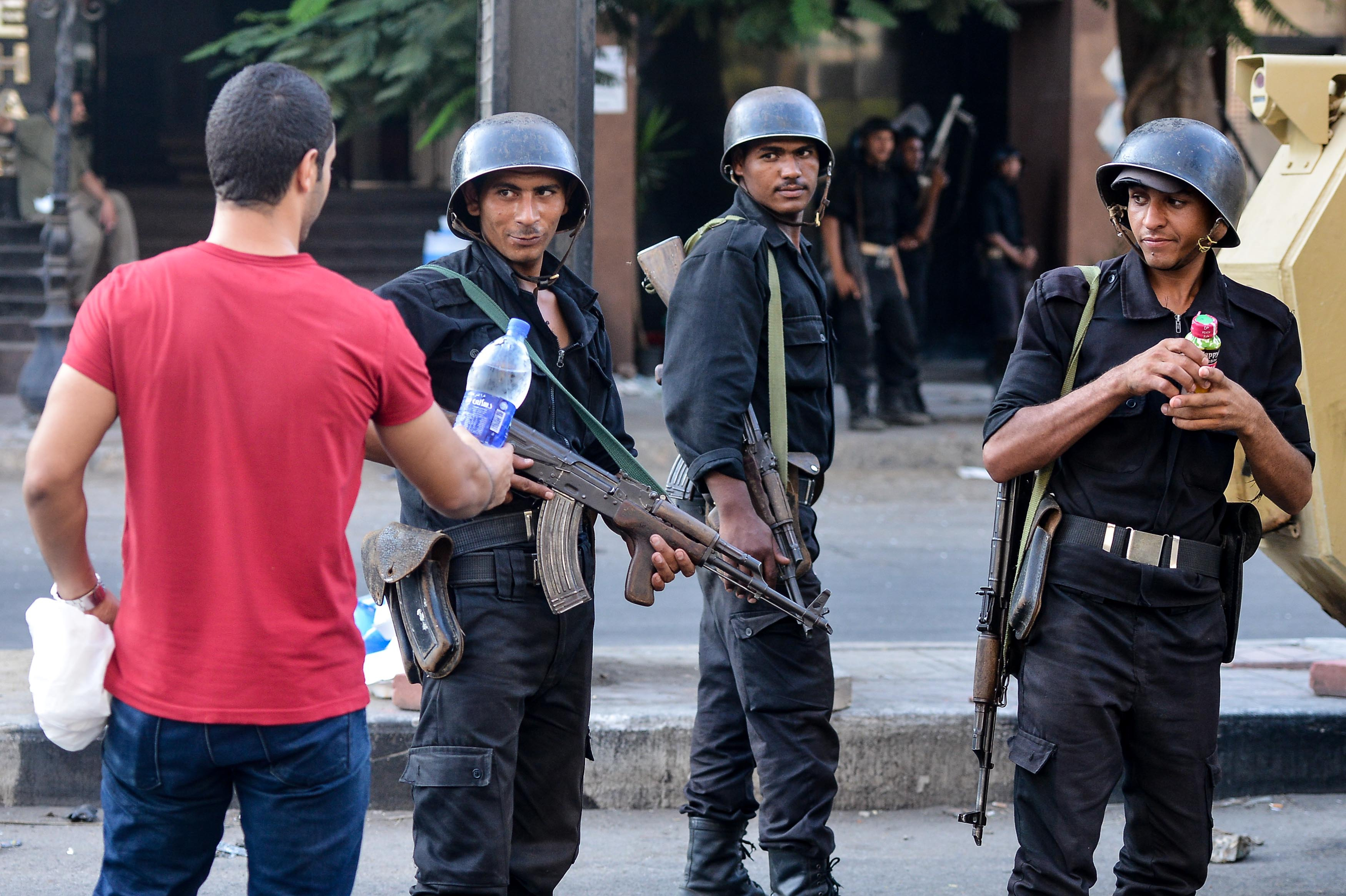 An Egyptian civilian (left) offers water to policemen during clashes with protesters in Cairo.