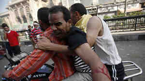 Supporters of the deposed Egyptian president, Mohammed Morsi, carry an injured demonstrator who was shot during clashes in Ramses Square in Cairo on Friday. Dozens were killed nationwide in escalating violence.