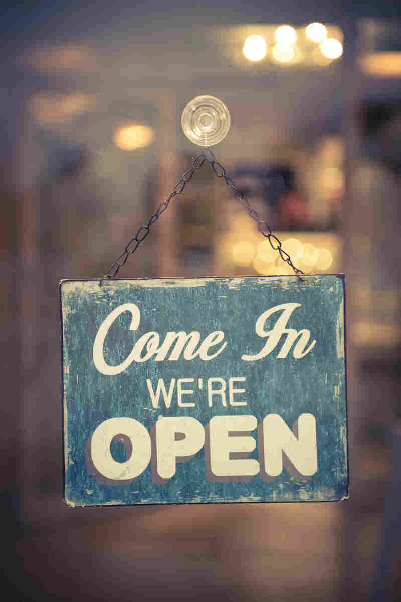 "A weathered sign hanging in a store window says, ""Come in; we're open."""