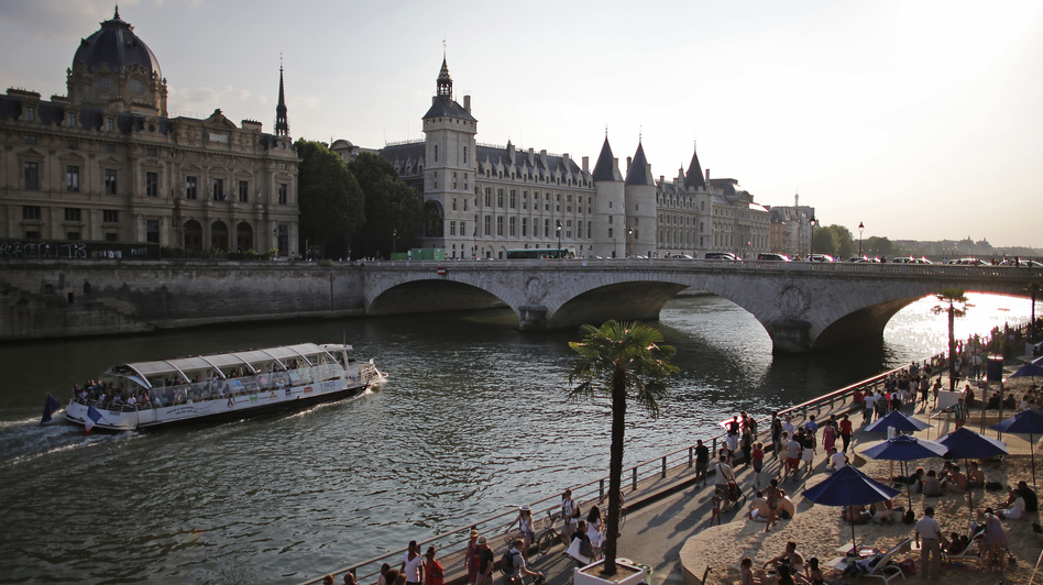 """People enjoy the sun next to Pont Neuf bridge as """"Paris Plage, or Paris Beach, opens along the banks of the Seine river in Paris, on July 20. The annual free event brings a half-mile of beach into the heart of the French capital. (Christian Hartmann/Reuters /Landov)"""
