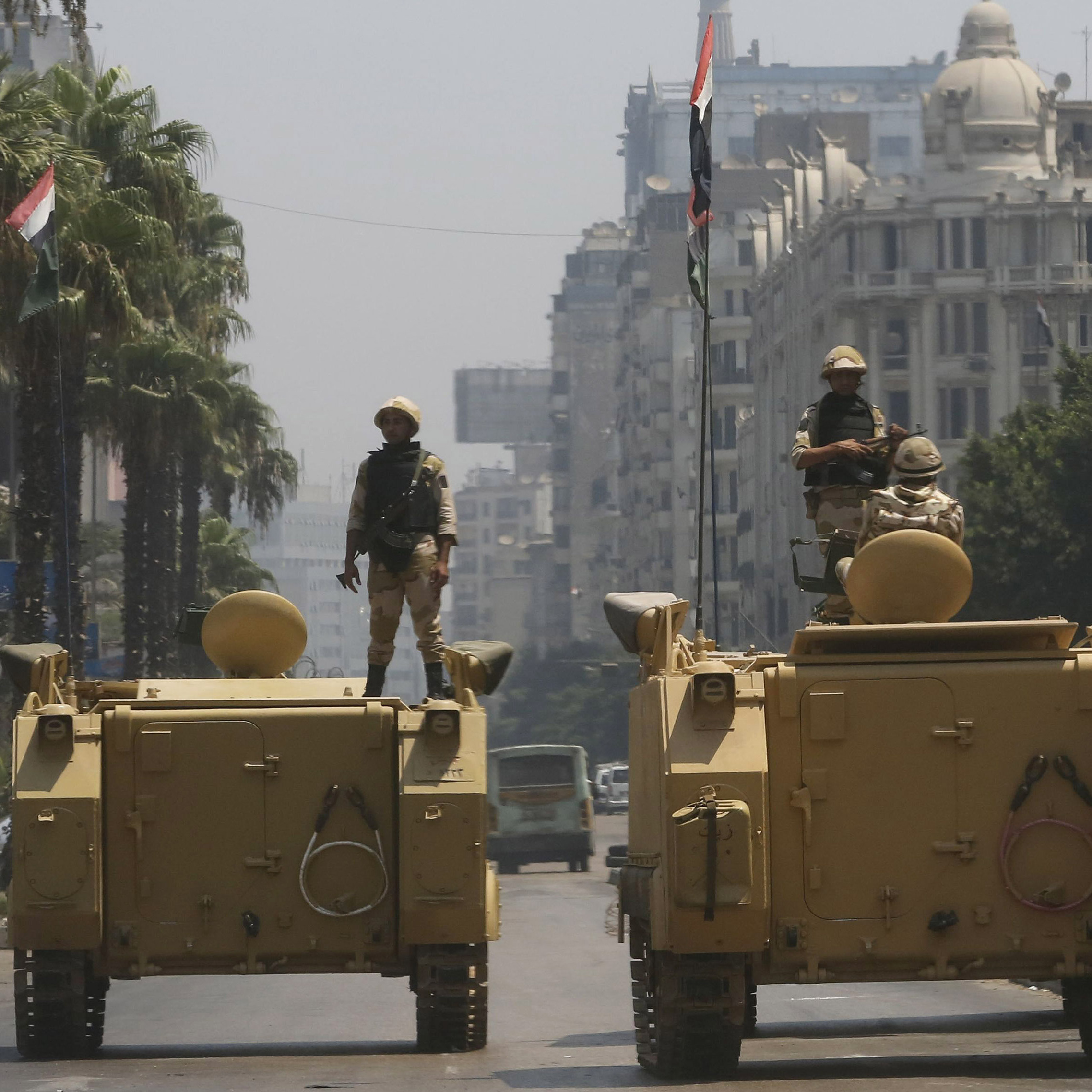 Soldiers stood atop armored personnel carriers outside the state-run television station in Cairo early on Friday.