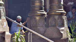 Egyptians shelter behind columns after police exchanged gunfire with supporters of ousted president Mohamed Morsi holed up inside a Cairo mosque on Friday.