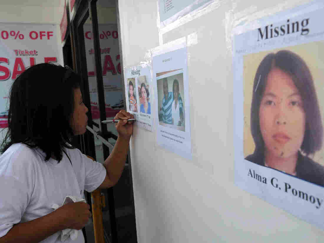 A relative of one of the missing passengers writes down contact numbers on Sunday at the office of the ferry involved in a collision, in Cebu City.