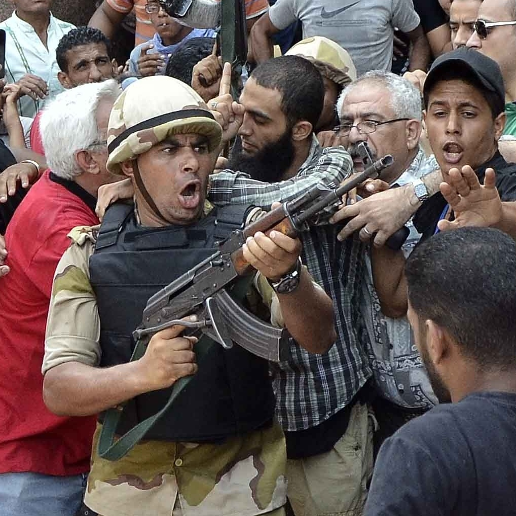 An army officer escorts an Islamist man from Cairo's Fateh mosque on Saturday. Islamist supporters of ousted president Mohamed Morsi holed up in the mosque on Friday, instigating a standoff with security forces surrounding the building.