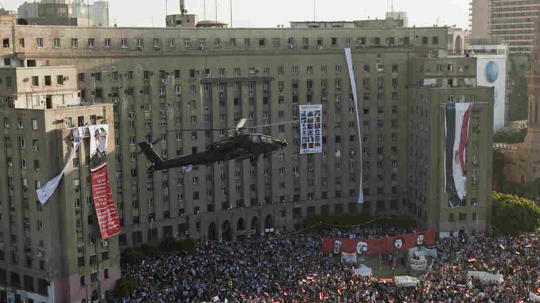 An Egyptian Apache helicopter flies over a crowd of pro-military demonstra