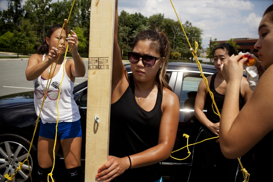 """Stephanie Moy, 23, (center) sets up a volleyball net with her teammates at a practice in Rockville, Md. Women's teams also compete in the North American Chinese Invitational Volleyball Tournament. """"CYC is a family thing,"""" she says, """"Our fathers played together. It's like tradition. I want my kids to play for CYC."""" (NPR)"""