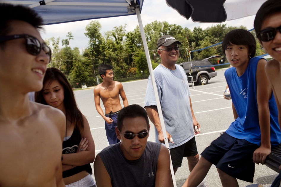 """Jeff Yuen, 53 (center), a financial controller for a government contractor, coaches younger 9-man players. """"We got involved because our dads would do this every Sunday,"""" he says. """"But once they left the cities to move to the suburbs, the Asian community started losing their roots. So we are trying to maintain our rich heritage."""" (NPR)"""