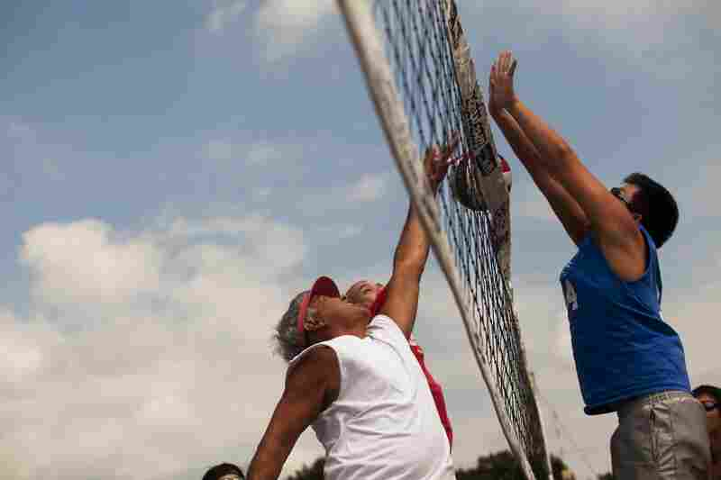 """Walter Wong, 63 (left, red visor) has been playing 9-man volleyball for 45 years. """"The kids now are much more advanced because they are starting around 12 years old,"""" Wong says."""