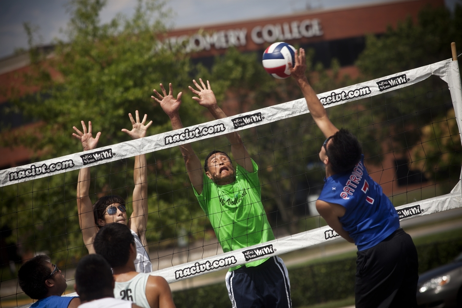 Sam Li, 52 (center, lime green) has been playing 9-man volleyball for nearly 30 years and keeps up with the younger players.