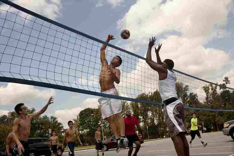 """Team co-captain Ceril Venegas, 17, (center) takes the ball over the net against Gerel Hall, 20, who practices with the Youngbloods. """"Usually [players] are smart enough not to dive"""" onto the asphalt or concrete 9-man court, Venegas says."""