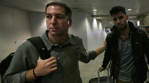 "Glenn Greenwald (left) and David Miranda after Miranda's arrival early Monday at Rio de Janeiro's International Airport. Miranda had been detained for 9 hours at London's Heathrow Airport. Authorities reportedly questioned him about Greenwald's reporting of the ""NSA leaks."""