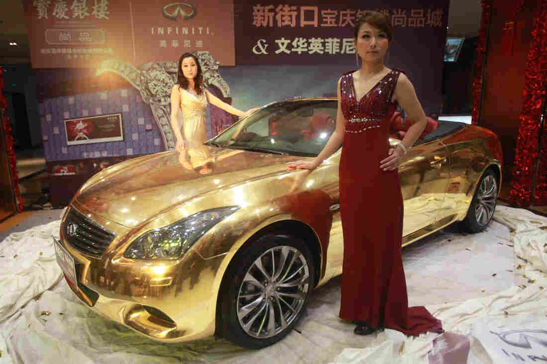 Models pose with a gold-plated Infiniti luxury sports car on display at a jewelry store in Nanjing, in east China's Jiangsu province, in 2011.