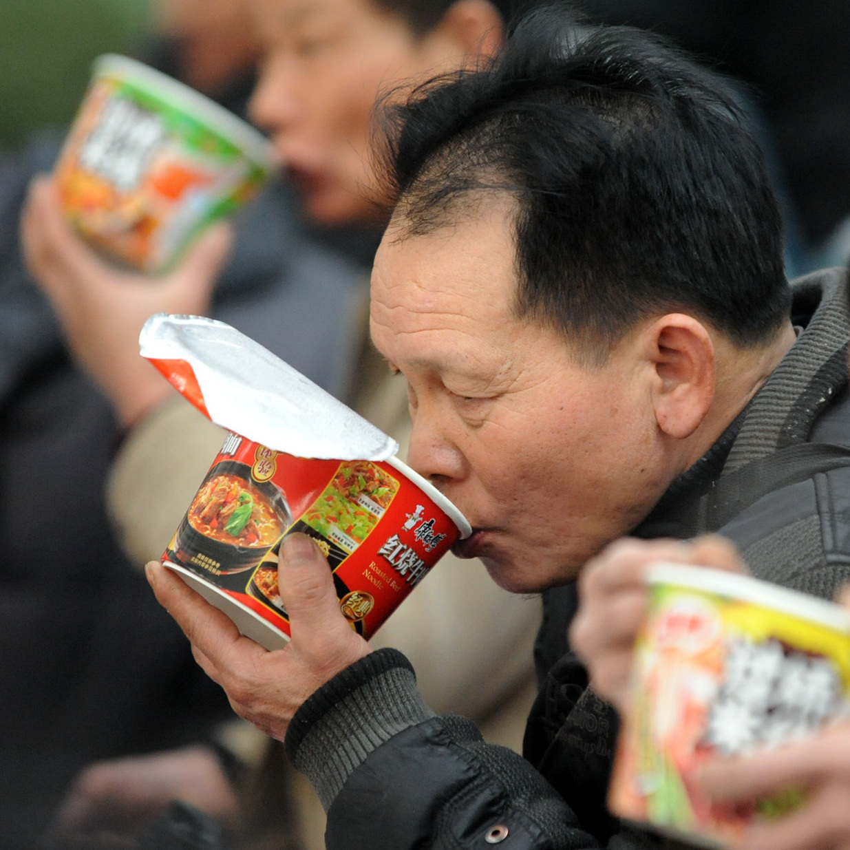 Passengers eat instant noodles at the railway station in Shenyang, China in January 2013.