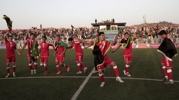 Afghanistan's soccer players dance to celebrate beating Pakistan, in a f