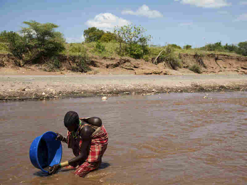 A South Sudanese woman, with a child on her back, pans for gold in the Singaita River in the eastern part of the country.