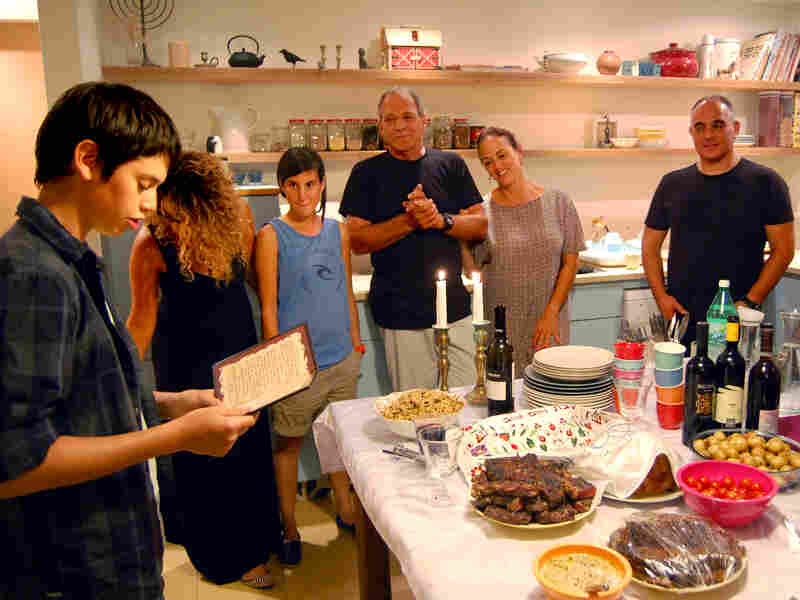 Calderon (center) looks on as her son reads the blessing before Friday night Shabbat dinner.