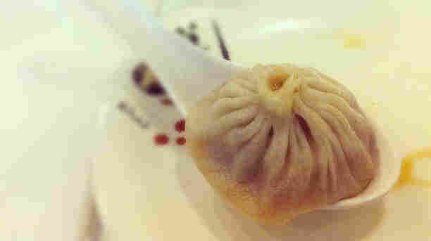 A xiao long bao, or soup dumpling, in a large spoon.