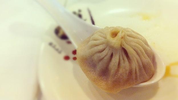 A xiao long bao, or soup dumpling, in a large spoon. (NPR)
